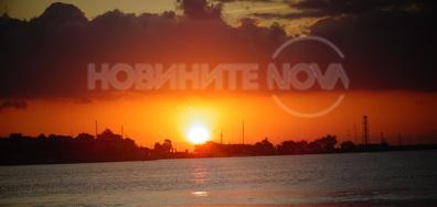 Изгревът ален, зад облак надвесен, изпраща към морската шир светлина