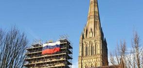 Окачиха огромен руски флаг на скеле край катедралата в Солсбъри